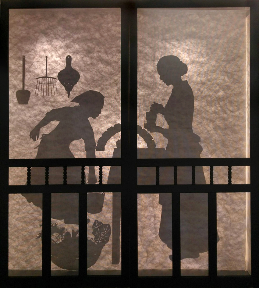 Silhouettes of two women working in an 18th century kichen with a hearth, tools, and vegetable basket